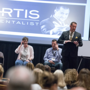 Curtis The Mentalist entertaining a corporate audience on stage during an in-person event.